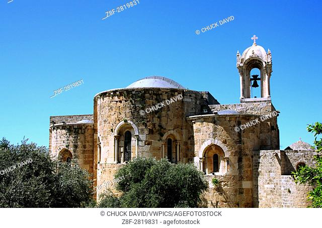 Historical stone church in Byblos, Lebanon features arches and ornate bell tower in the tourist district