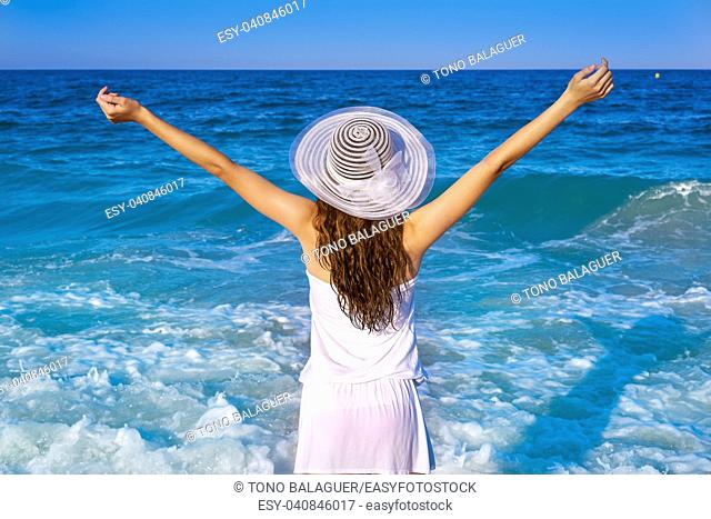 Girl with beach hat in sea open arms with summer white dress