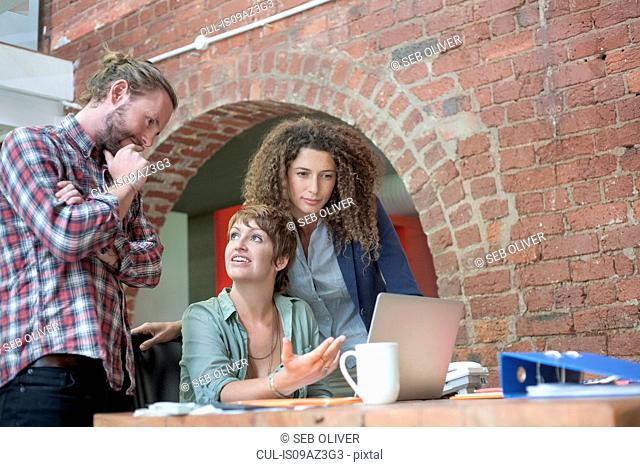 Woman explaining to team at desk meeting in creative studio