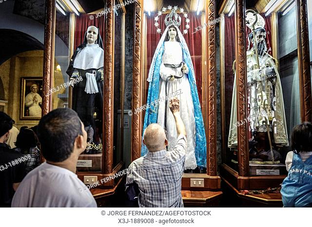 People praying in front of an statue of The Virgin Mary inside The Basilica Minore del Santo Niño, Cebu, Philippines