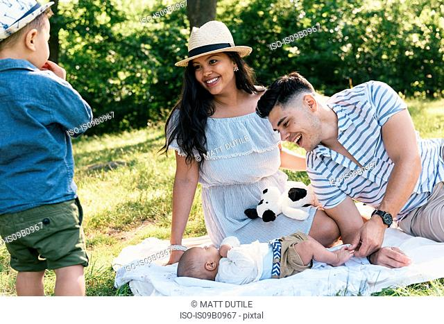 Parents relaxing with baby and toddler sons on picnic blanket in Pelham Bay Park, Bronx, New York, USA