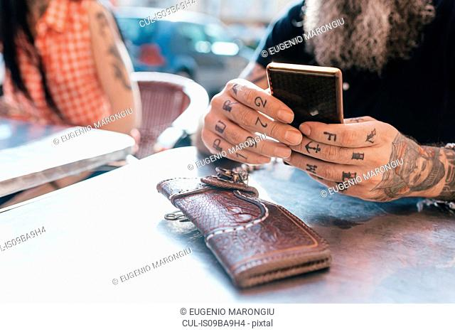 Mature hipster man using smartphone at sidewalk cafe, close up of tattooed hand