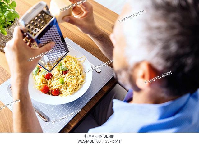 Man grating parmesan on his pasta