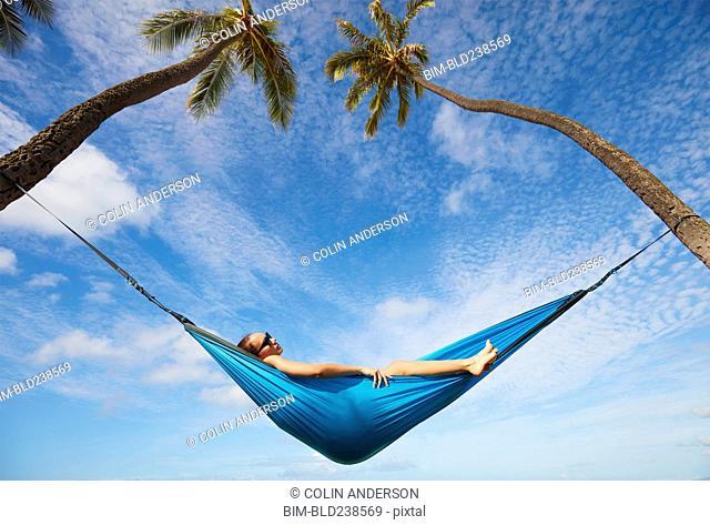 Pacific Islander woman laying in hammock between palm trees