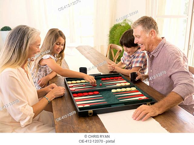 Grandparents and grandchildren playing backgammon