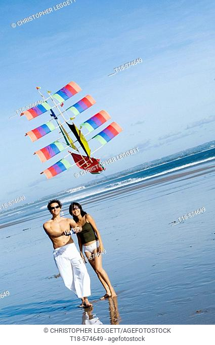 couple playing kite on beach