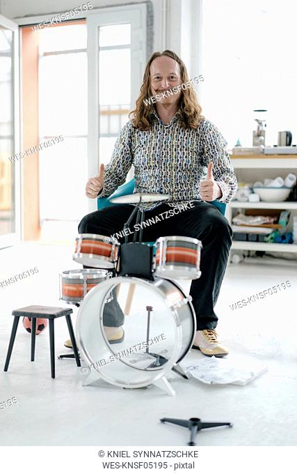 Portrait of confident man sitting at toy drums