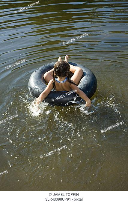 Girl on inflatable ring in lake
