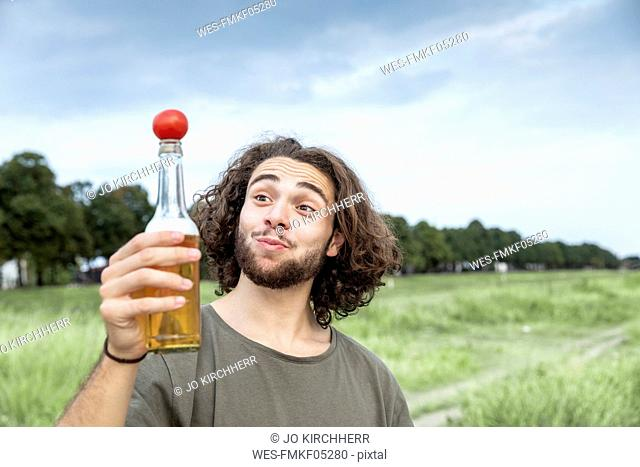 Portrait of smiling young man outdoors balancing tomato on beer bottle