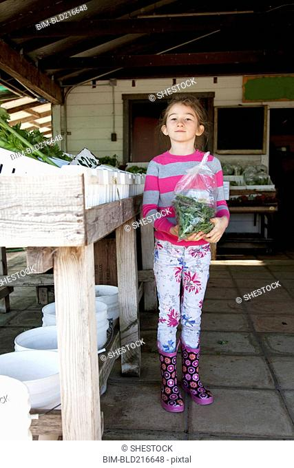 Mixed race girl holding bag of produce in farmers market