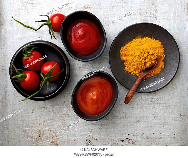 Tomatoes, curry powder, chili ketchup, and tomato ketchup in bowls