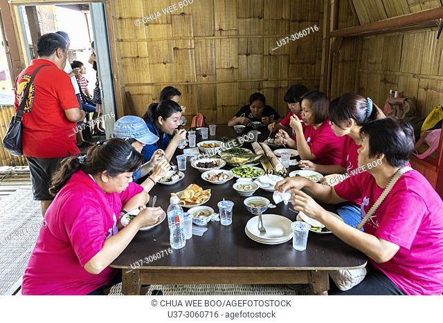 Tourists having lunch during Gawai celebration at Annah Rais's long house, Sarawak, Malaysia