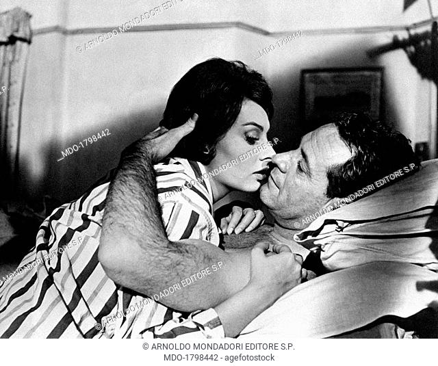 The Italian actress Sophia Loren and the American actor William Holden look at each other embraced on a bed, in a scene of the movie The Key by Carol Reed