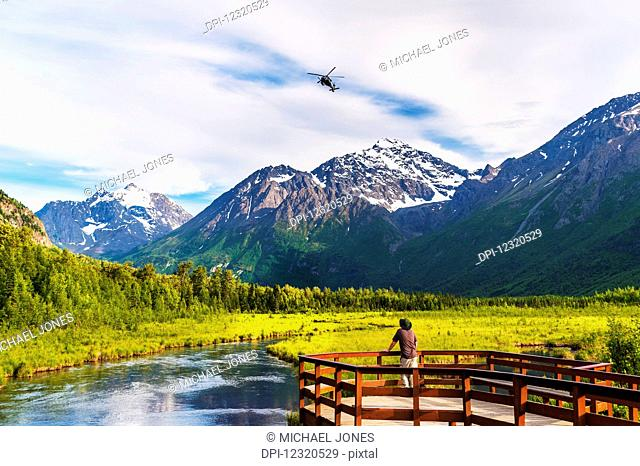A man is standing on the Eagle River Nature Center boardwalk while a Black Hawk helicopter flies over head in the Chugach State Park in Southcentral Alaska, USA