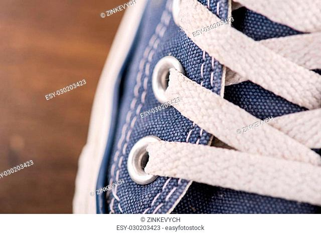 cool blue gym shoes with white laces on brown parquet wooden floor close up