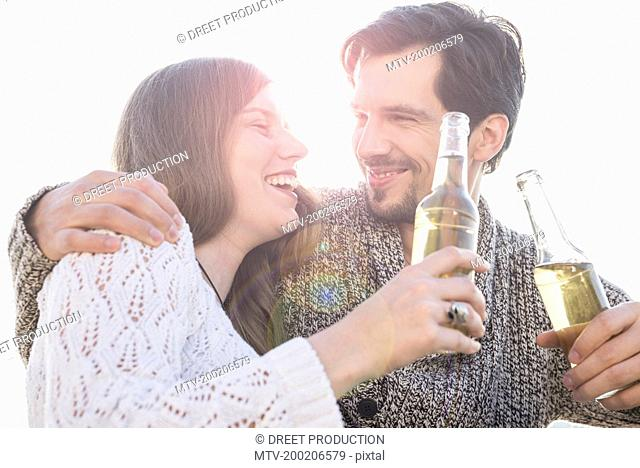 Young couple fun laughing sunset drinking beer