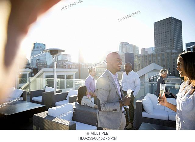 Business people drinking champagne socializing sunny urban rooftop