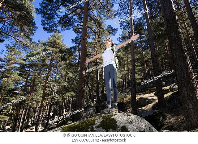 hiker sport woman standing on a great rock in the forest, open arms, in Navacerrada mountain, Guadarrama Natural Park, Madrid, Spain