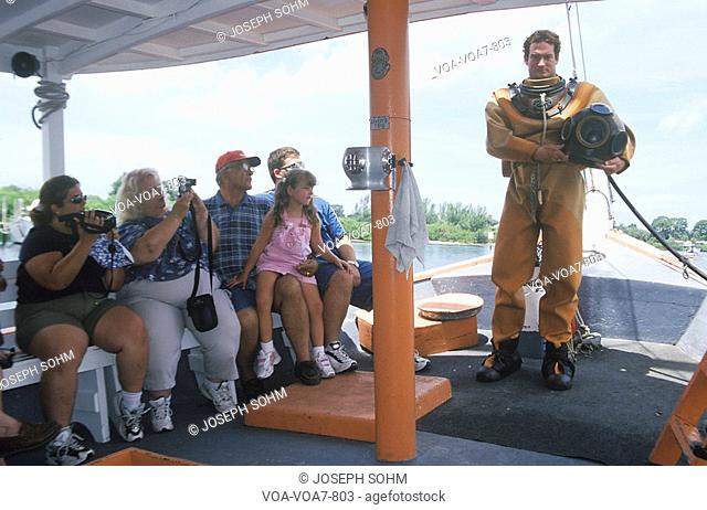 Greek sponge diver talks to tourists on boat in historic diving suit in Tarpon Springs FL