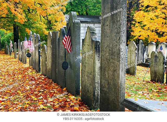 Historic graves are covered with fallen autumn leaves in Vermont