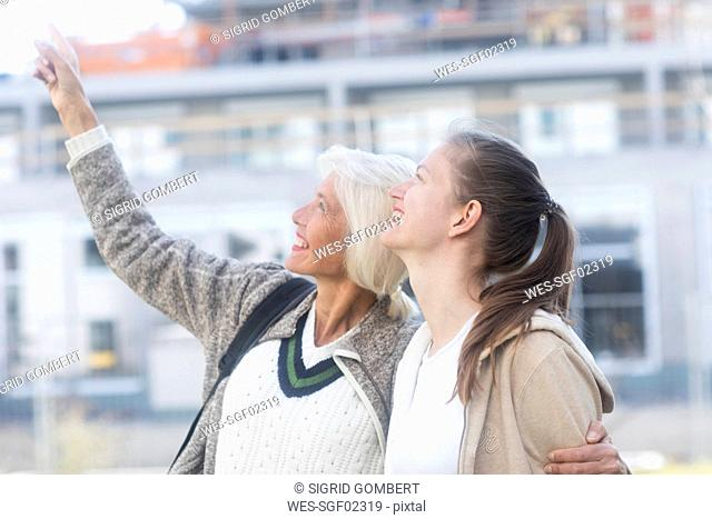 Profile of mother and adult daughter watching something together