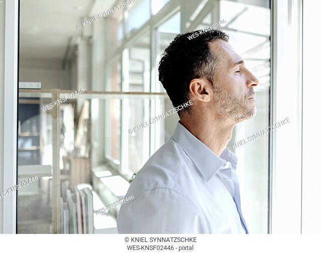 Businessman with closed eyes at the window