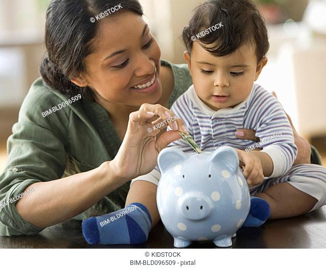 Mixed race mother and baby boy putting money in piggy bank