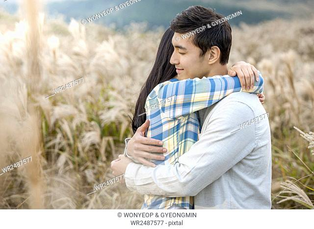 Side view portrait of young romantic couple hugging each other in silver grass field