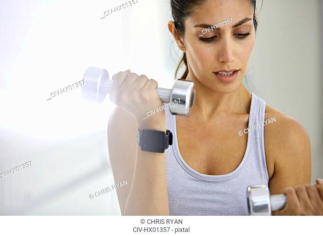 Focused woman doing biceps curls with dumbbells