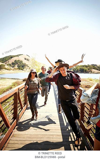 Friends running on footbridge in park