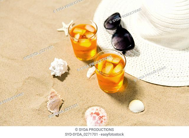 cocktails, sun hat and sunglasses on beach sand