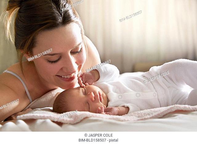 Mother admiring newborn baby on bed