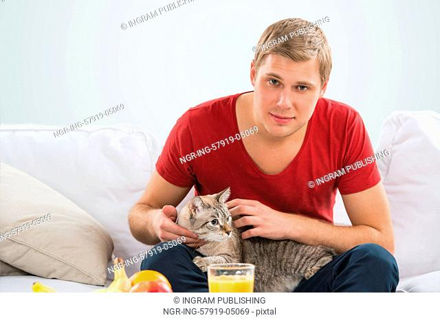 Man and a cat at home. Handsome man cuddling his tabby cat on sofa