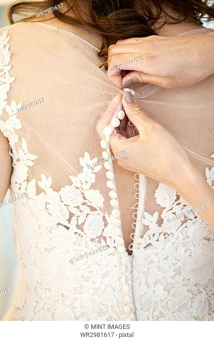 Hands doing up the small buttons on the back of a wedding dress with a net bodice and lace detail. A bride getting ready