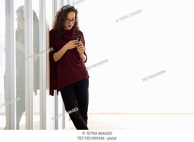 Young woman leaning on glass wall and text messaging