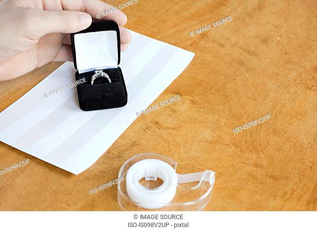 Person wrapping engagement ring