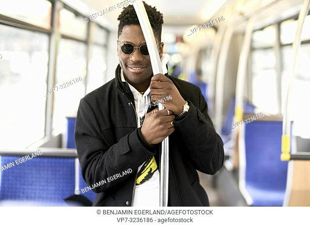 young man in tram, public transport, in Munich, Germany
