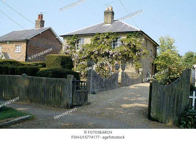 Topiary in garden beside gravel drive to Victorian detached village house with wisteria