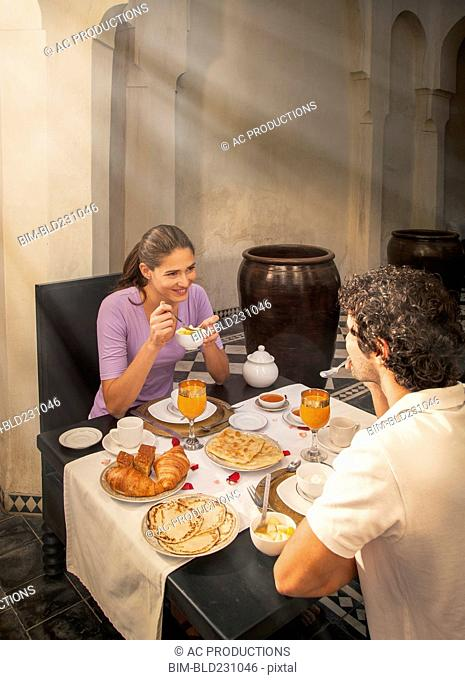 Smiling Caucasian couple eating at table