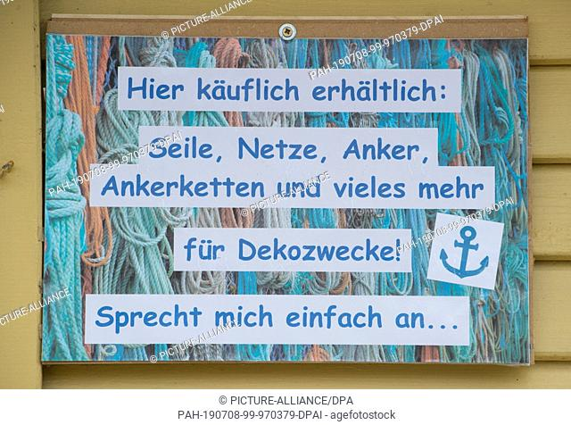 """05 July 2019, Mecklenburg-Western Pomerania, Freest: In the harbour, a sign with the words """""""" Available for sale here: ropes, nets, anchors"""