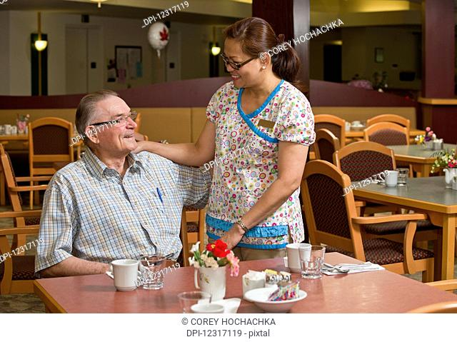 Senior citizen and caregiver in cafeteria; Devon, Alberta, Canada