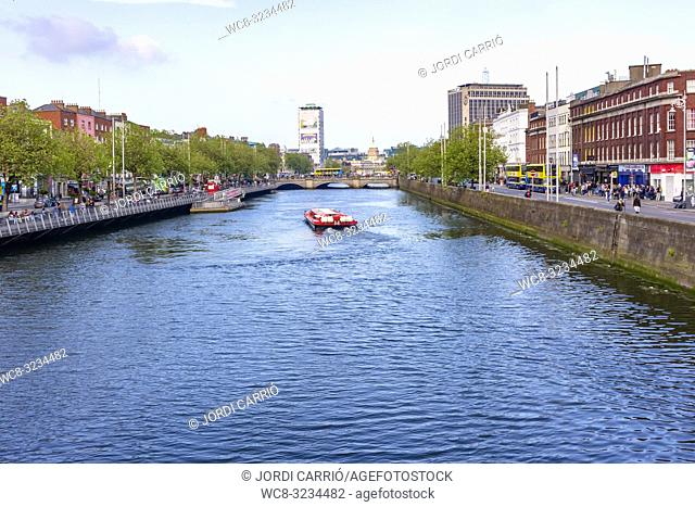 DUBLIN, IRELAND: View of the Liffey river in Dublin, where a barge sails