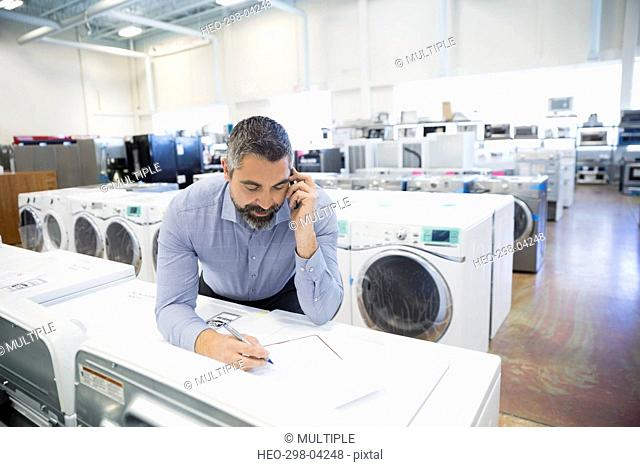 Salesman with clipboard talking on cell phone in appliance store