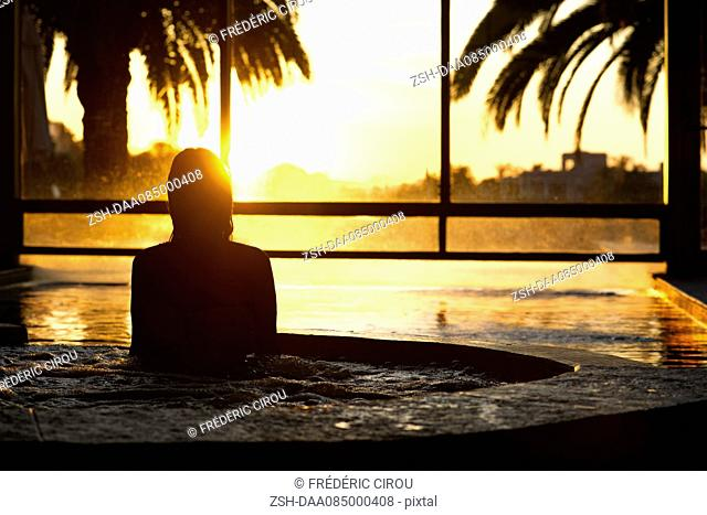 Woman in indoor pool during sunset