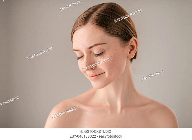 Calm and beautiful. Portrait of redhead woman with freckles keeping eye closed and smiling while standing against grey background