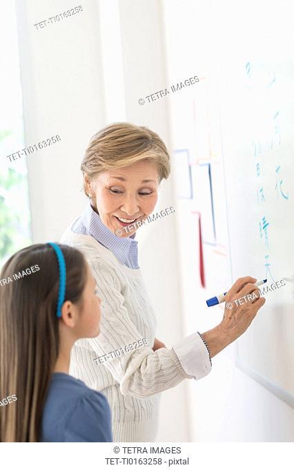 Teacher and schoolgirl (8-9) writing at whiteboard