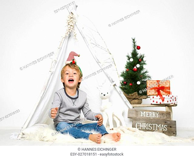 christmas scene with blond young and small christmas tree