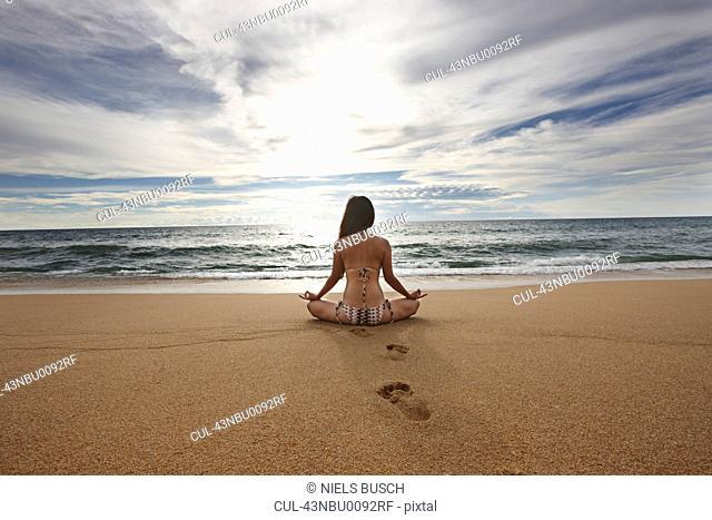 Woman meditating on sandy beach