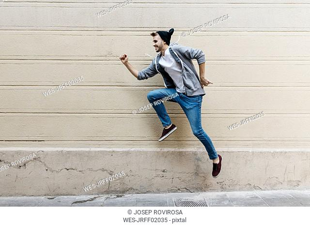 Happy young man jumping in front of a wall