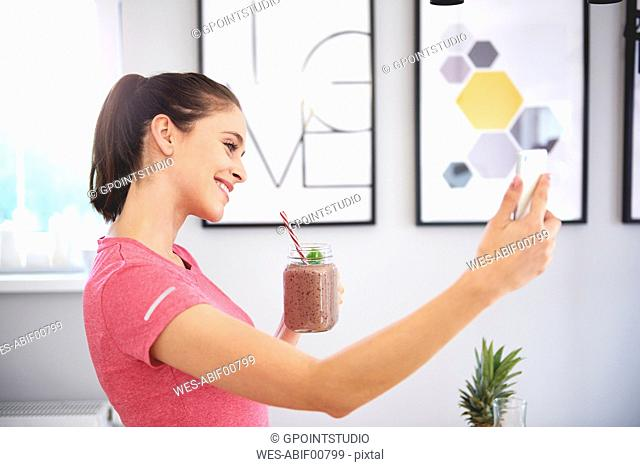 Smiling young woman with smoothie taking selfie with smartphone in the kitchen